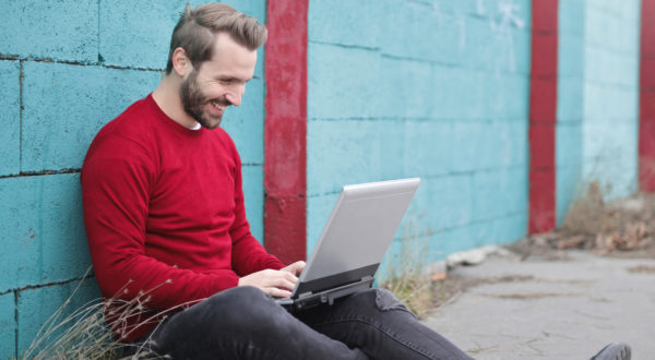 man working on a laptop leaning against a concrete wall